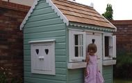 Childs playhouse with wooden cedar shingles, opening windows and window boxes
