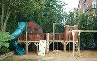 Treehouse with platforms, tube slide, climbing wall, firemans pole, monkey bars and tyre swings
